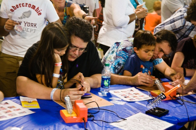 Dads and kids join in the soldering workshop at the Orlando Maker Faire
